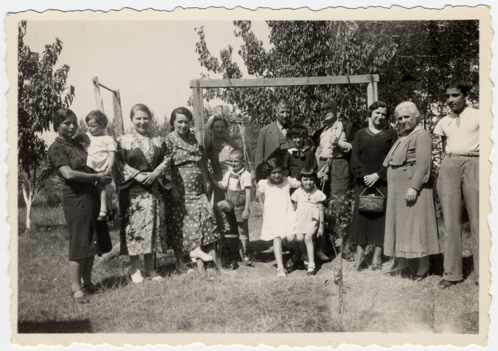 Picture of a large extended Bulgarian Jewish family at the Farhi's summer villa in Bankia, near Sofia.  Grandmother Luna (Farhi) Meranda is pictured second from the right.  Albert Farhi is in the center, next to the swing.  Moise is held by the family's housekeeper.