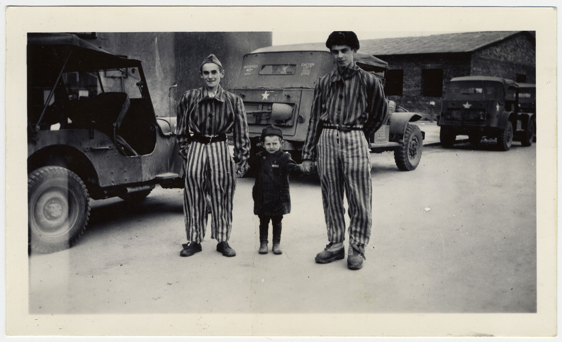 Josef Schleifstein poses with two survivors at Buchenwald.  Original caption reads:  Youngest person -- 4 yrs old 3 yrs in Buchenwald!