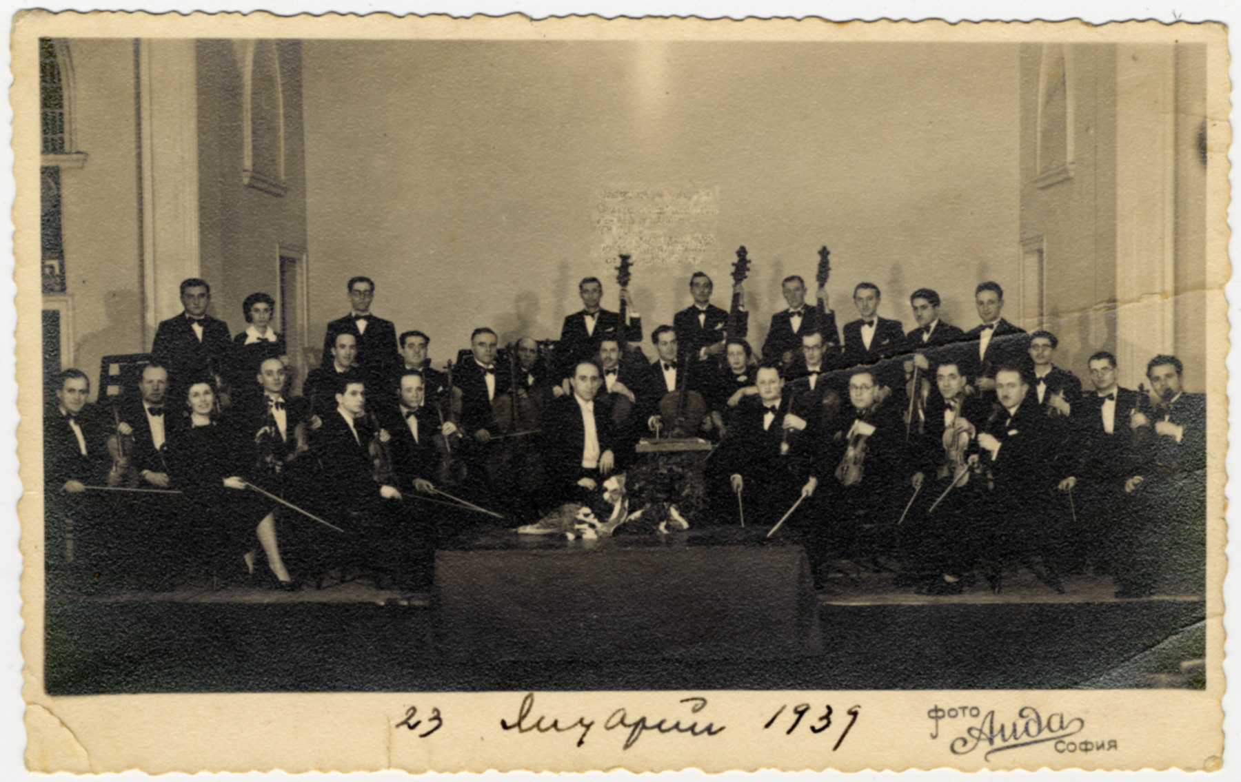 Studio portrait of the strings section of The Jewish Symphony Orchestra of Sofia.  The conductor is Mario Menashe Bronza, and the concert master is Leon Suroujon (who after WWII became the Director of the Musical Academy of Sofia).  Nissim Farhi is seated in the second row, fifth from the left.