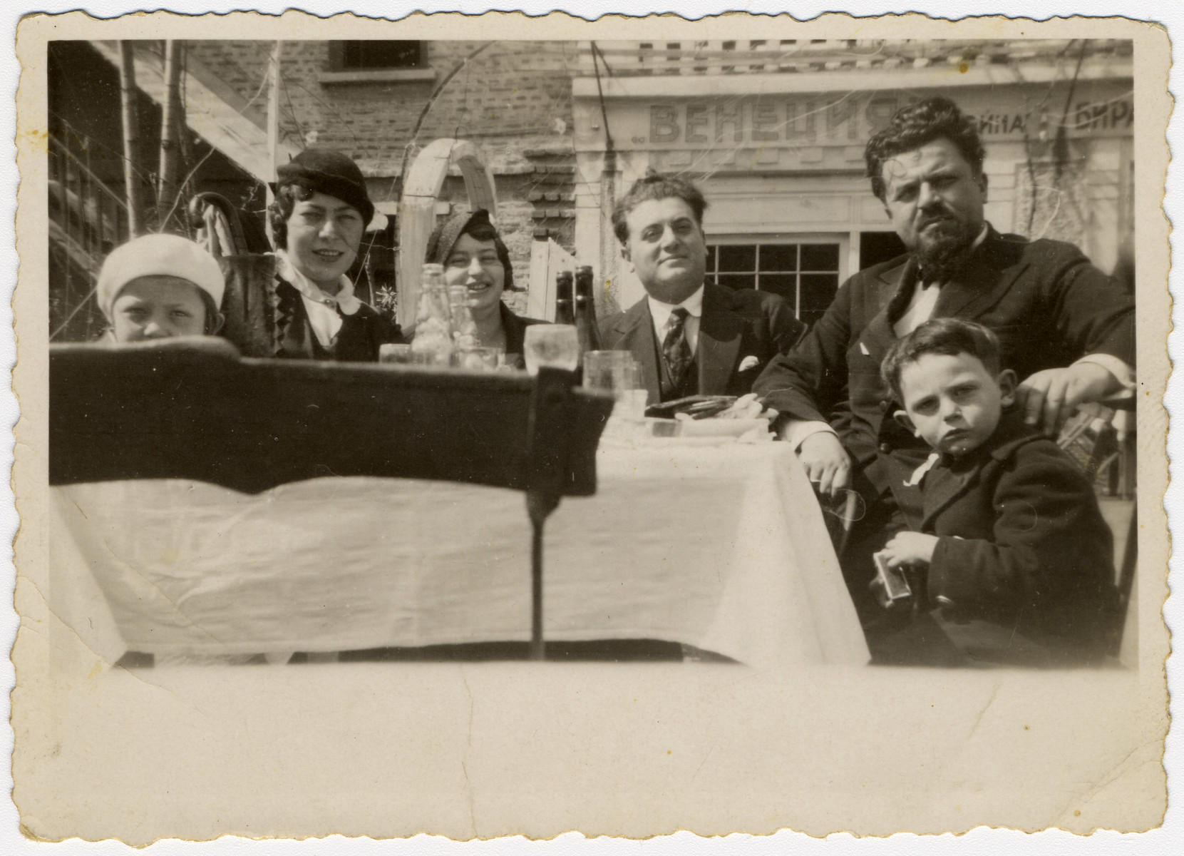 Two Bulgarian Jewish families sit around a table and share a meal.  From left to right are Rosie Hananel, Rachel Hananel, Caroline Farhi, Nissim Farhi, Rabbi Asher Hananel (the Chief Rabbi of Bulgaria and neighbor of the Farhi's) and Albert Farhi.