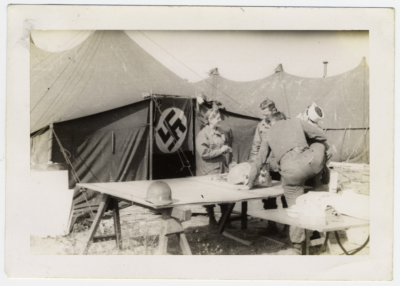 Group of American soldiers congregate in front of a tent displaying a Nazi flag as a door.   Original caption reads:  Nazi flag makes a good tent flap.    Heading above photographs:  The 120th set up in suburban Race Track near Frankfurt a/m April 5-15.