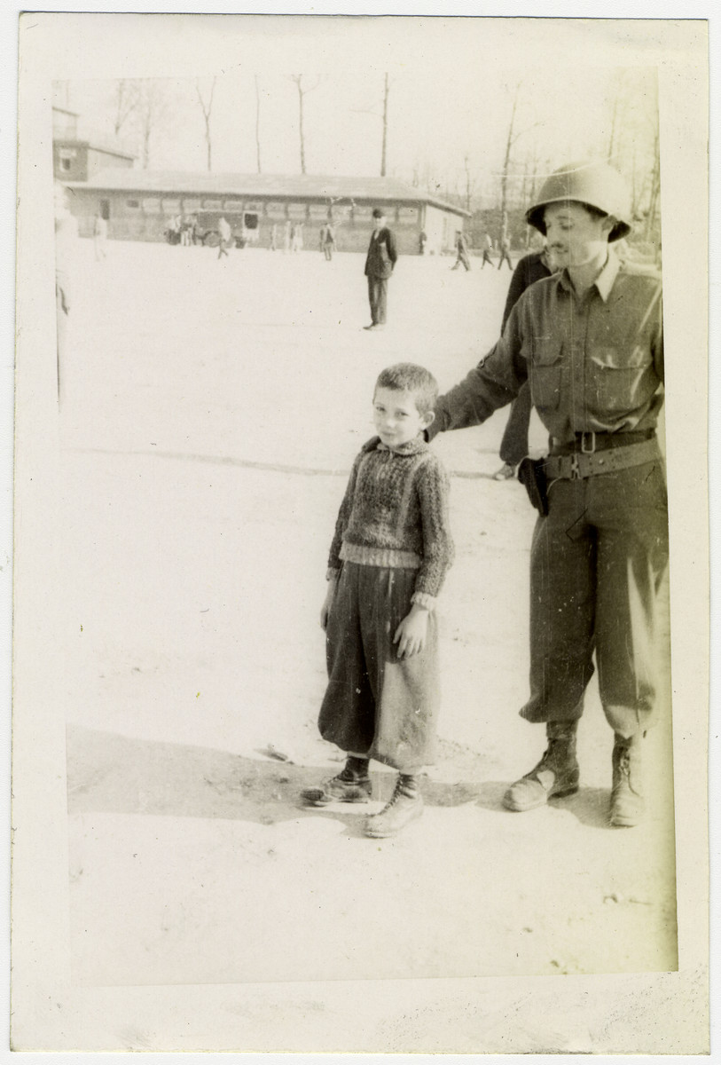 Young survivor of Buchenwald poses with a soldier.