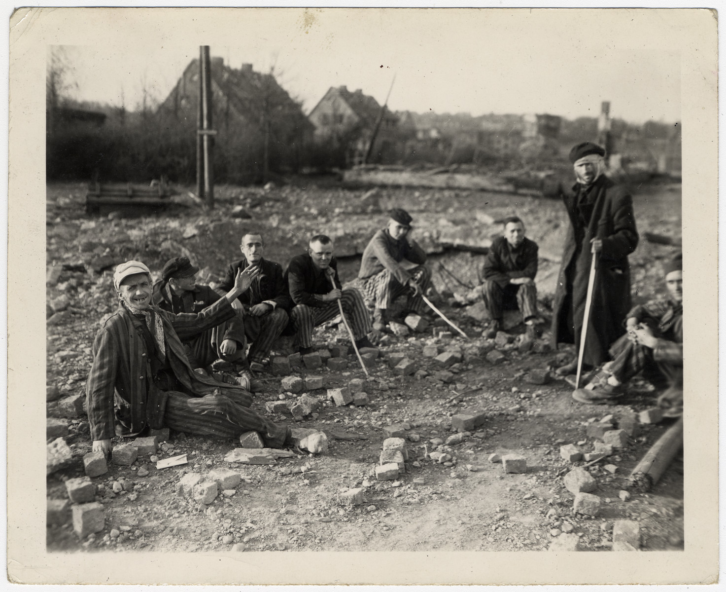 Survivors sit amidst the rubble of the Nordhausen concentration camp.