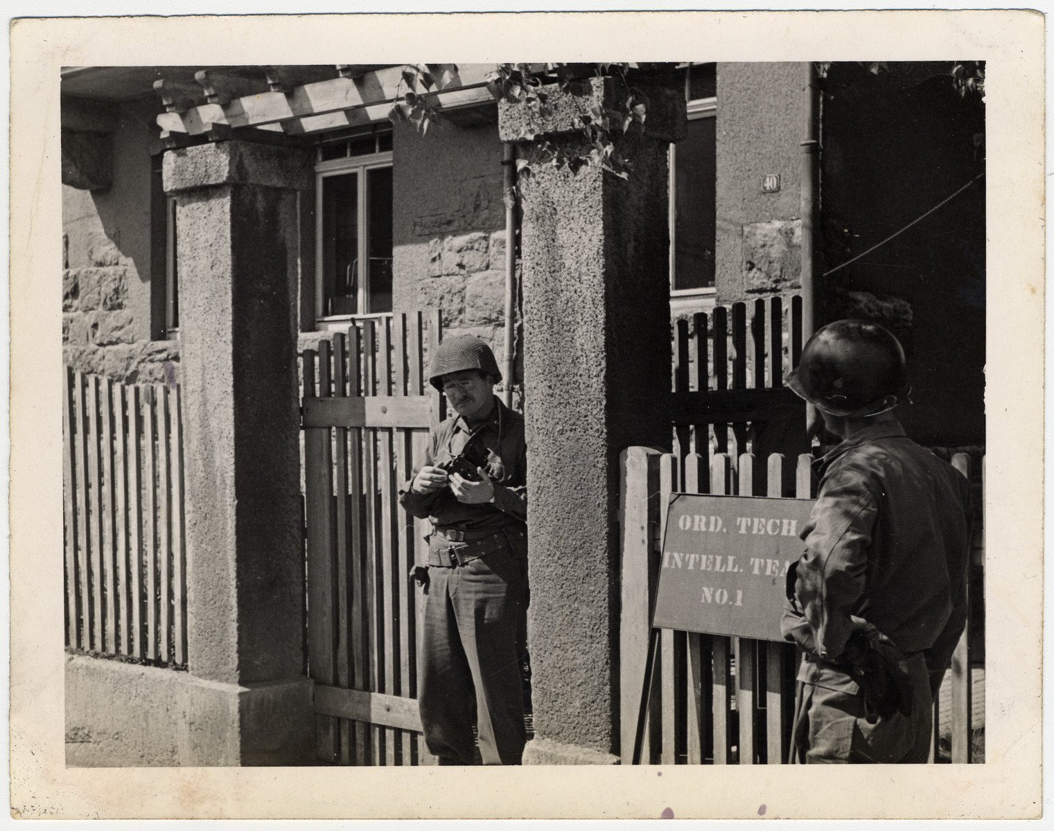 William Bostwick Curtis stands by the headquarters of the Ord. Tech Intelligence Team holding his camera.
