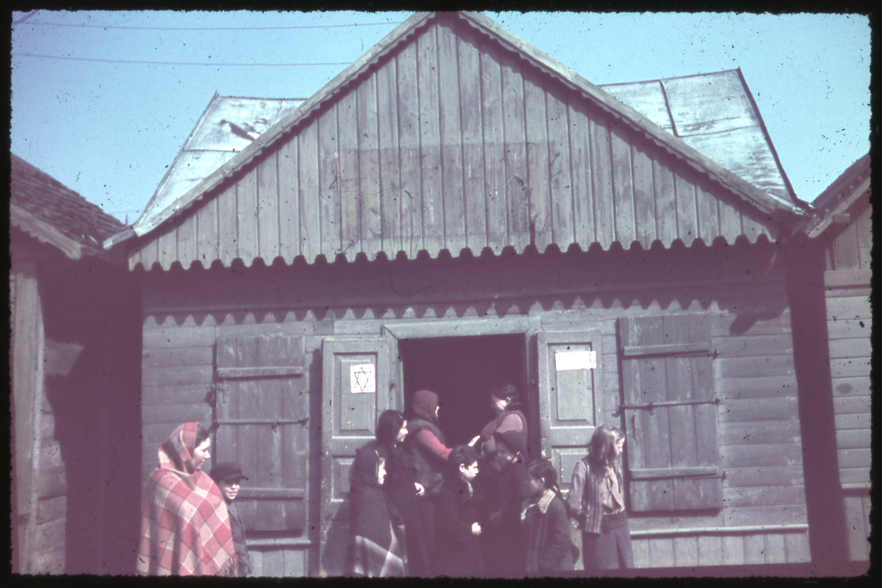 A group of women and children enter a wooden building marked with a Jewish star.
