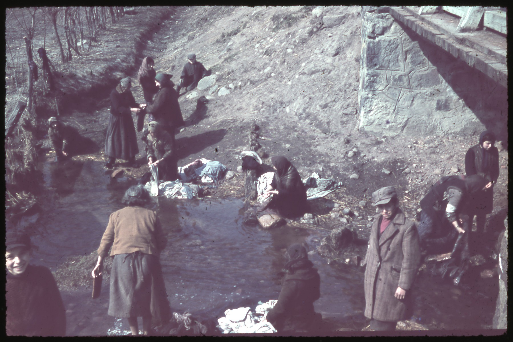 Women, some wearing armbands, wash their laundry in the Zagorzonka River.