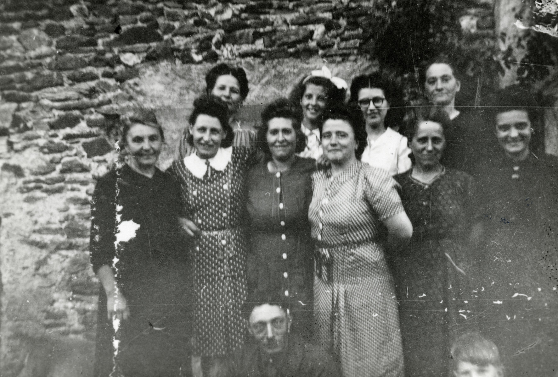 Nine women and a girl pose outside a building.   Pictured second from the left is Rosa Moses, mother of the donor. Jean Gasser is sitting down in front of the group.