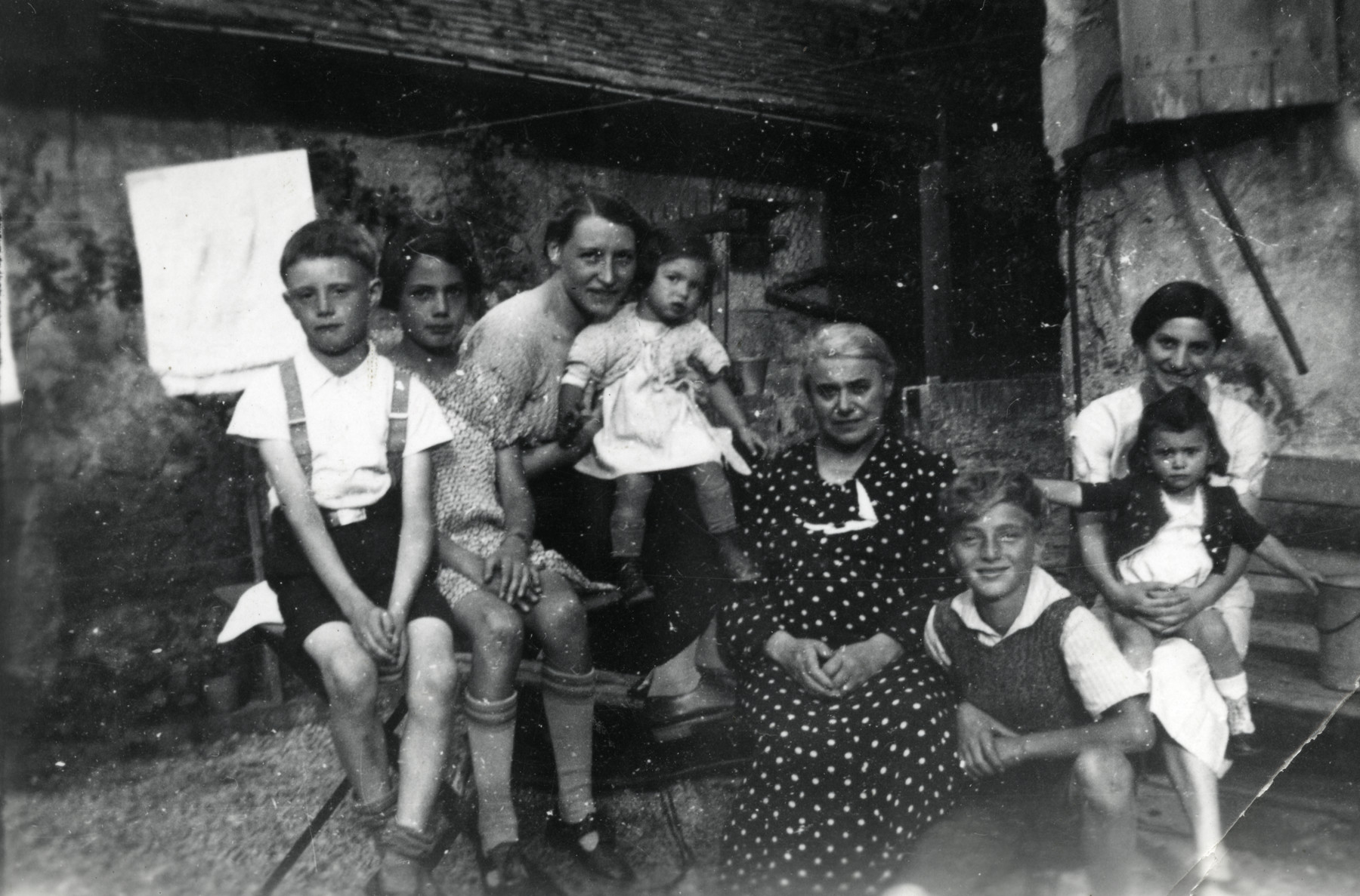 Members of an extended family pose outside a building on a farm.   Pictured third and fourth from the left is Rosa Moses, the donor's mother, and the donor Beatrice Heffes. Third from the right is Gerard Horst Meyerfeld, the donor's cousin.
