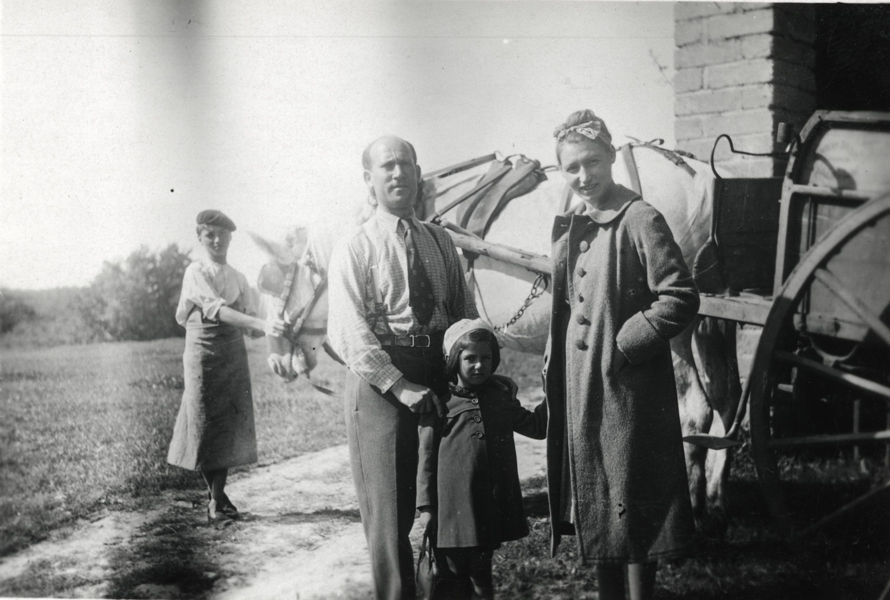 Group portrait  of Beatrice Heffes, her mother Rosa Moses, her cousin Gerard Horst Meyerfeld, and her uncle Sygmund Friedman, then visiting from Lyon. They are posing near a horse-drawn carriage, probably in front of a stable. Gerard is holding the horse's bit.