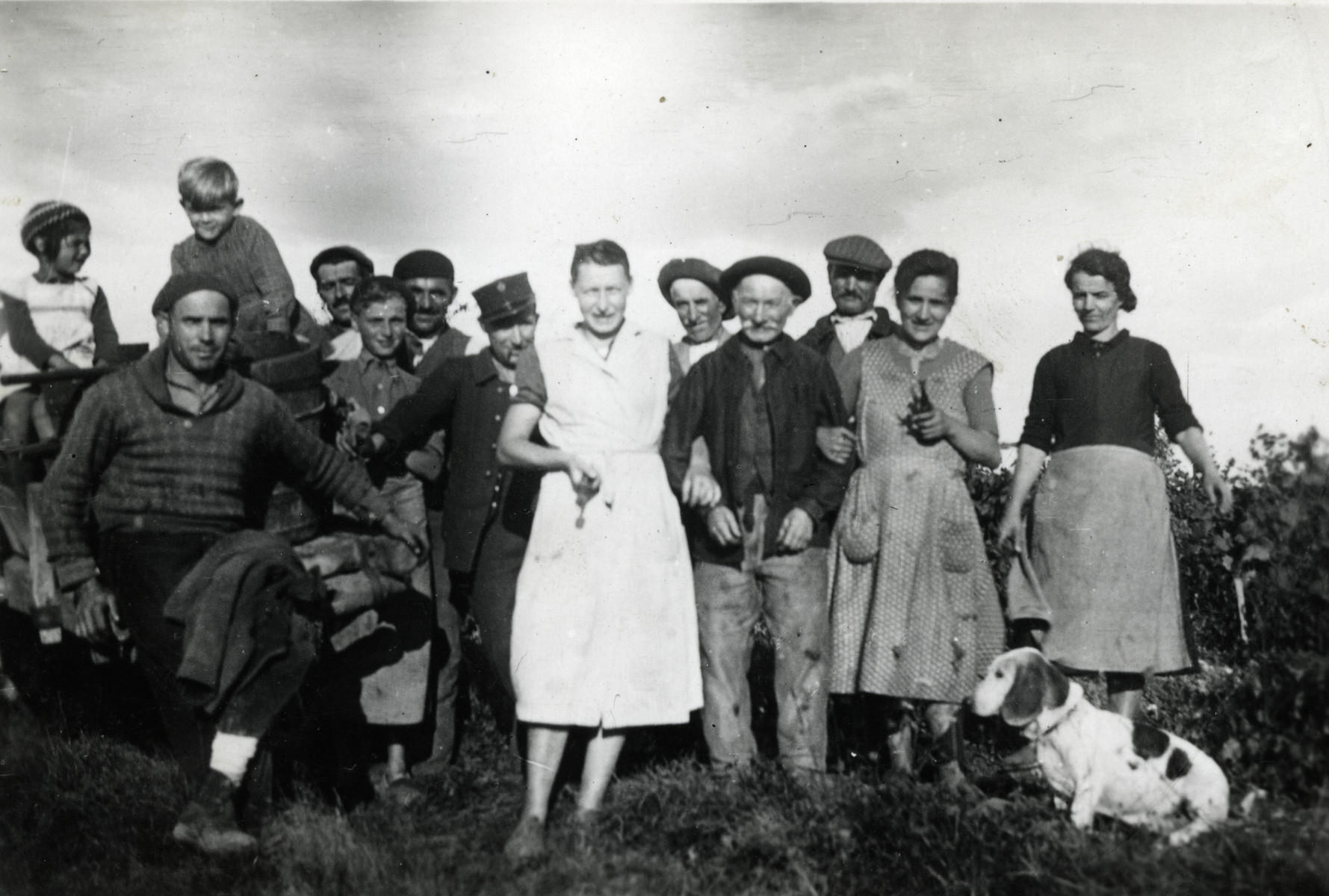 A group of thirteen people poses in front of a vineyard.   Pictured on the left is the donor, Beatrice Hoffer. In the center is her mother, Rosa Moses. Pictured in the back are Mr. Taffeler and Mr. Combes, the farmers who were hiring Beatrice's father, Alfred Kahn. Gerard Horst Meyerfeld, Beatrice's cousin, is standing in front of them.