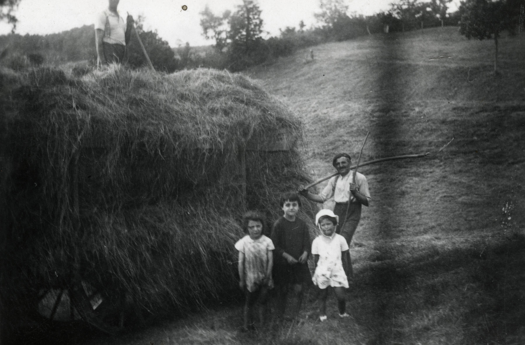Beatrice Heffes, her father's employer Mr. Combes, and his two daughters pose in front of a haystack. Another farmer can be seen standing on top of the haystack.