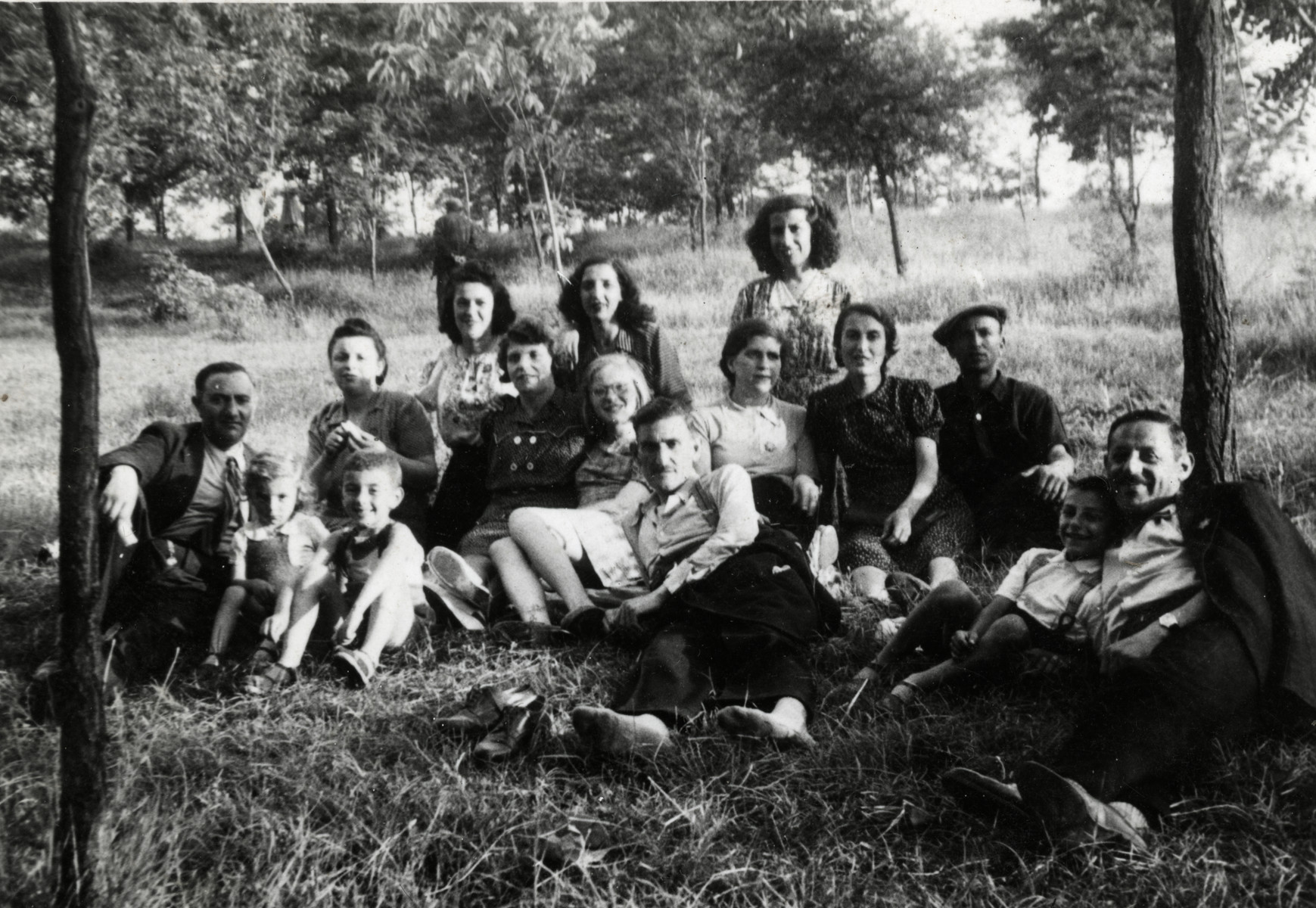 Several Jewish families who had lived together in temporary living quarters after their expulsion to Haskovo, relax on the grass.  Reine Behar and her parents are pictured in the center.