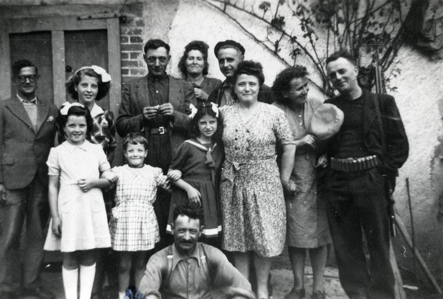 Four children and eight adults pose outside a building.   Pictured in the middle is Beatrice Heffer. Jean and Maria Gasser stand behind her, next to Beatrice's father, Alfred Kahn.