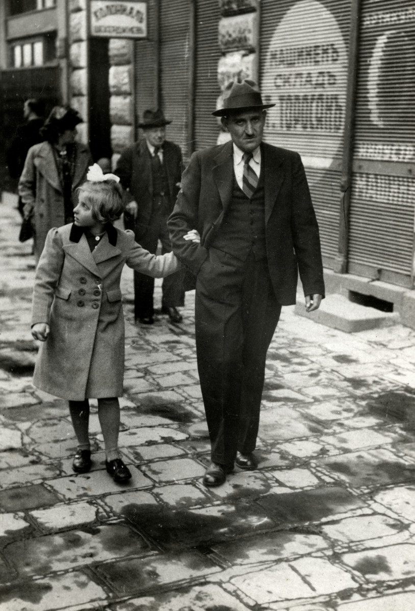 Reine Behar walks down a commercial street in Sofia holding her father's hand.  Her mother and grandfather are behind her.