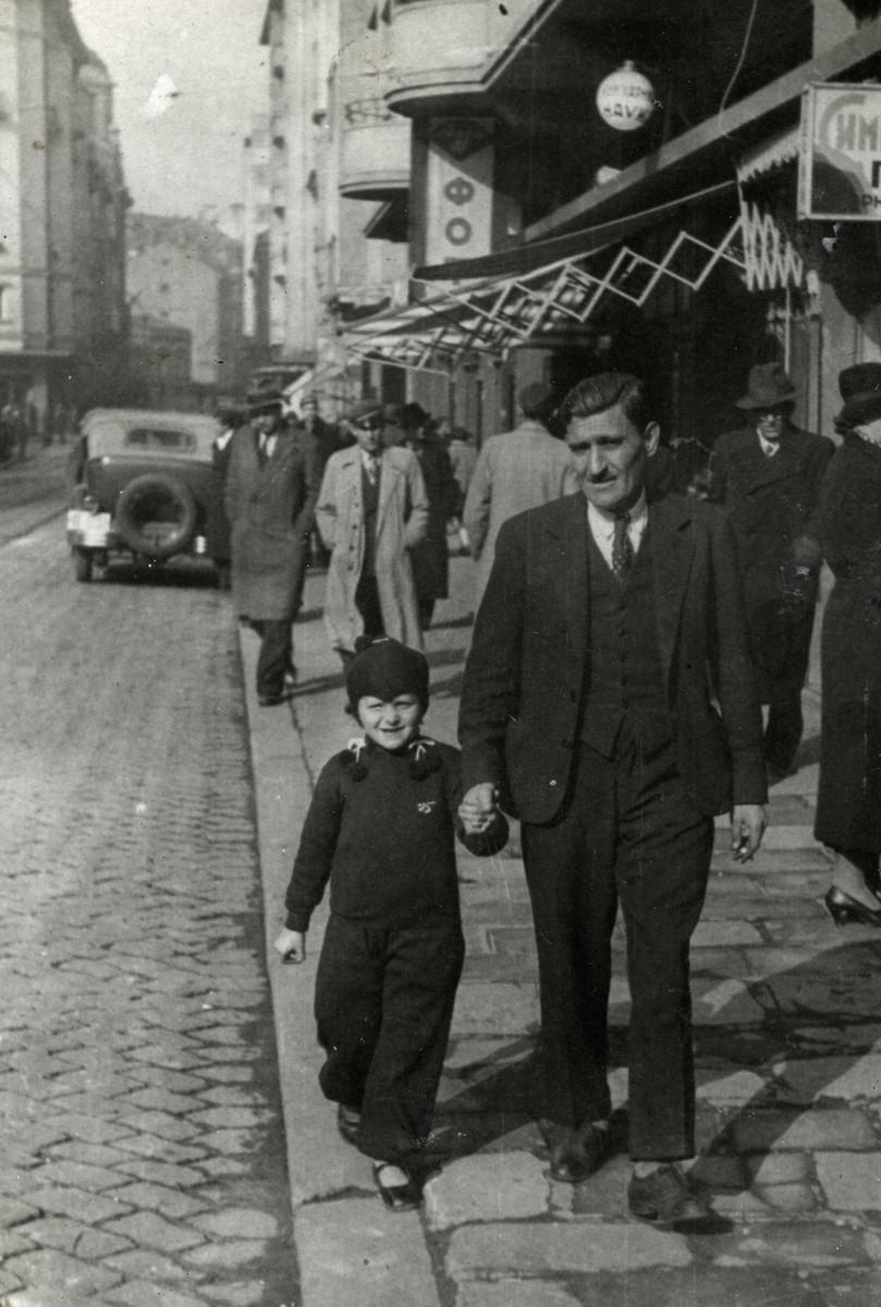 Reine walks down a street in Sofia hand in hand with her father Rachamin Behar.