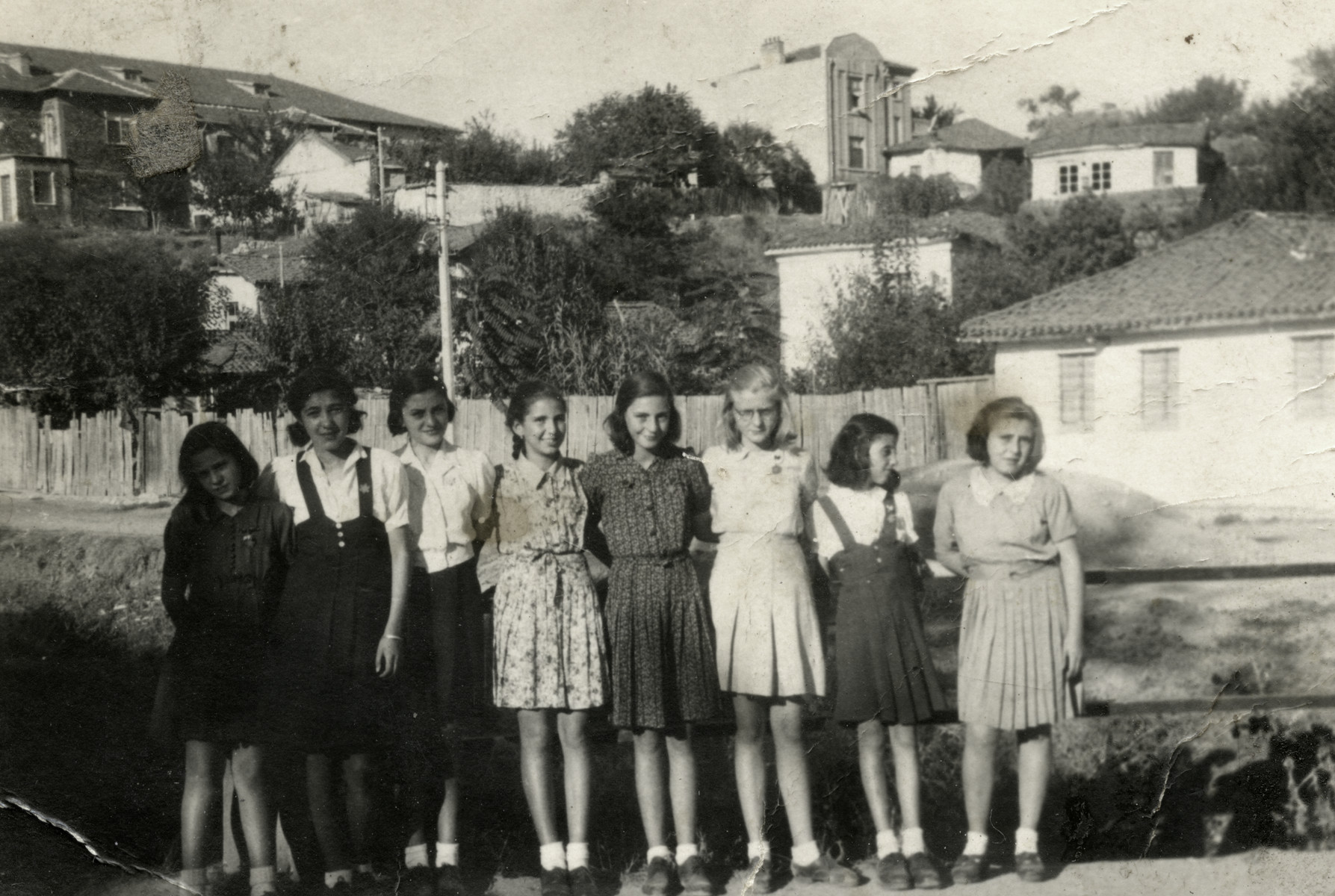 Group portrait of Jewish school girls outdoors in Haskovo; all are wearing Jewish stars.  Reine Behar is pictured third from the right.