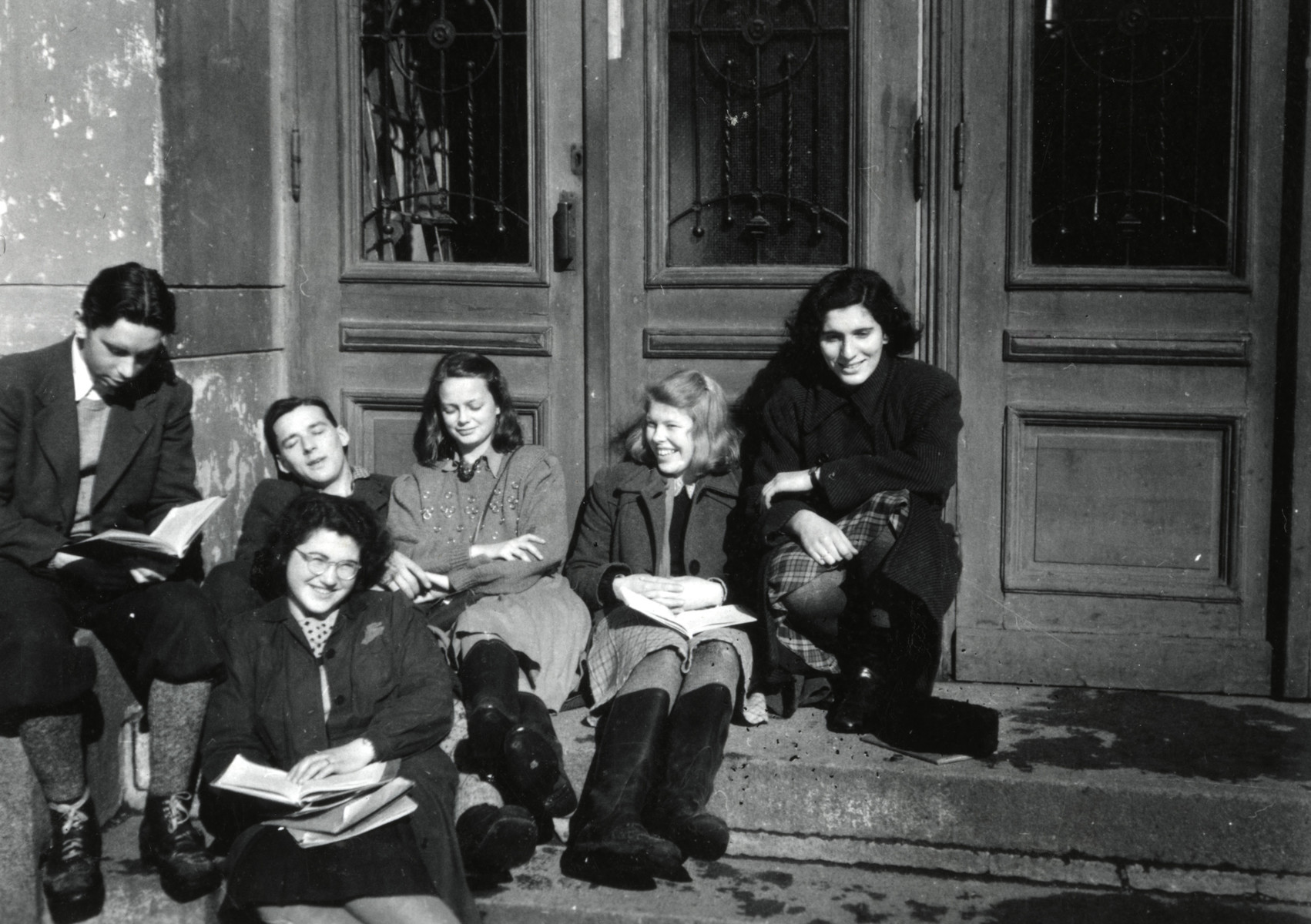High school students sit on the the steps of the Vestheim School for Girls in Oslo, Norway.  Celia Century is in the front row holding a book.  Rachel (Tulla) Blomberg is in the back row in a dark coat.