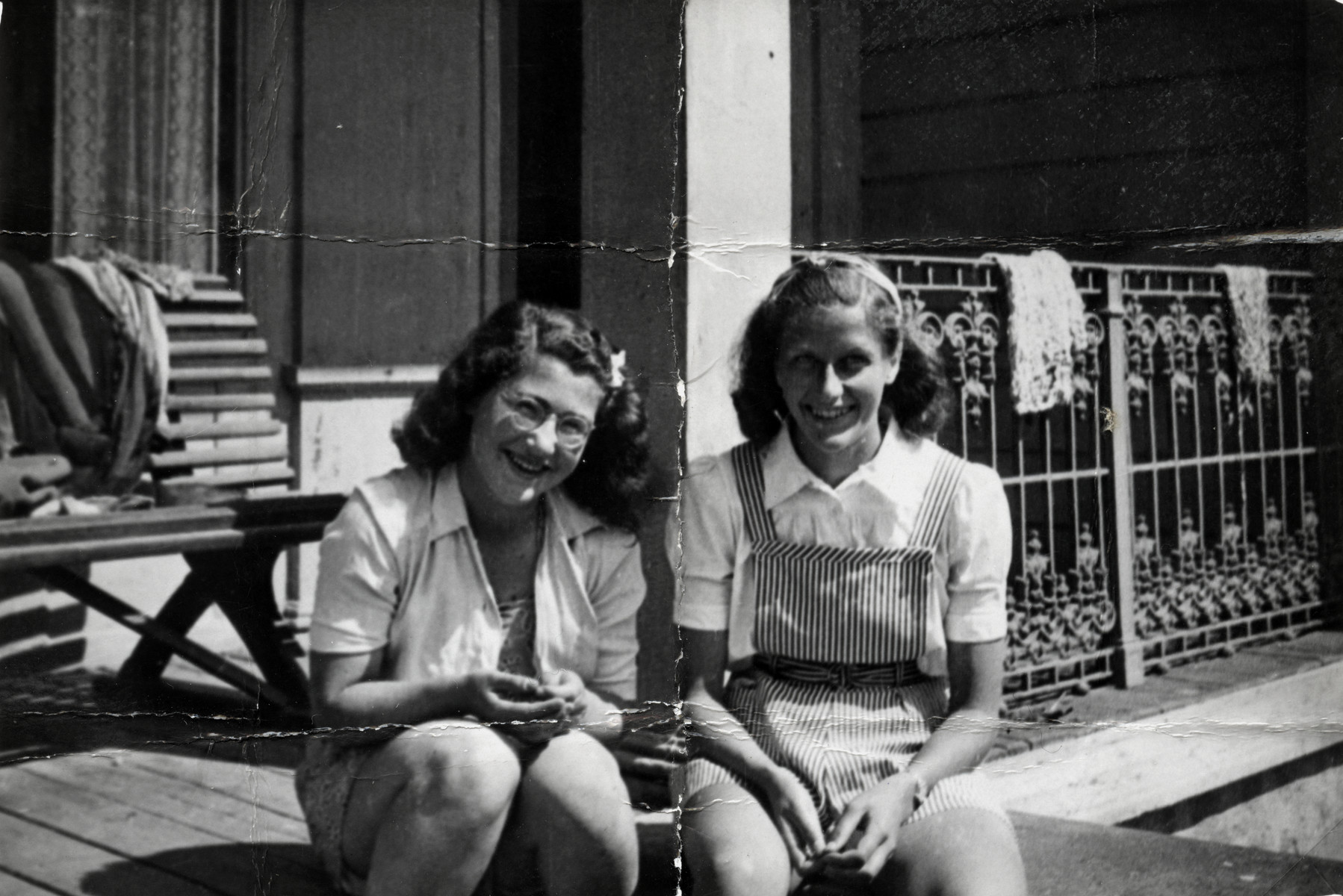 Celia Century, a Jewish refugee from Norway, sits a the deck of a summer camp in Ronneby Sweden next to a non-Jewish friend.