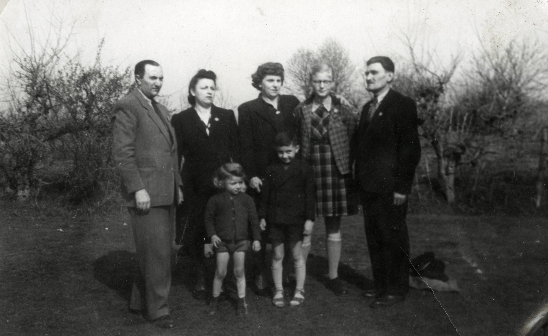 Two Jewish families pose outdoors in Haskovo wearing Jewish stars.  On the left is the family of Nissim Alvas.  On the right are Rachel, Reine and Rachamin Behar.