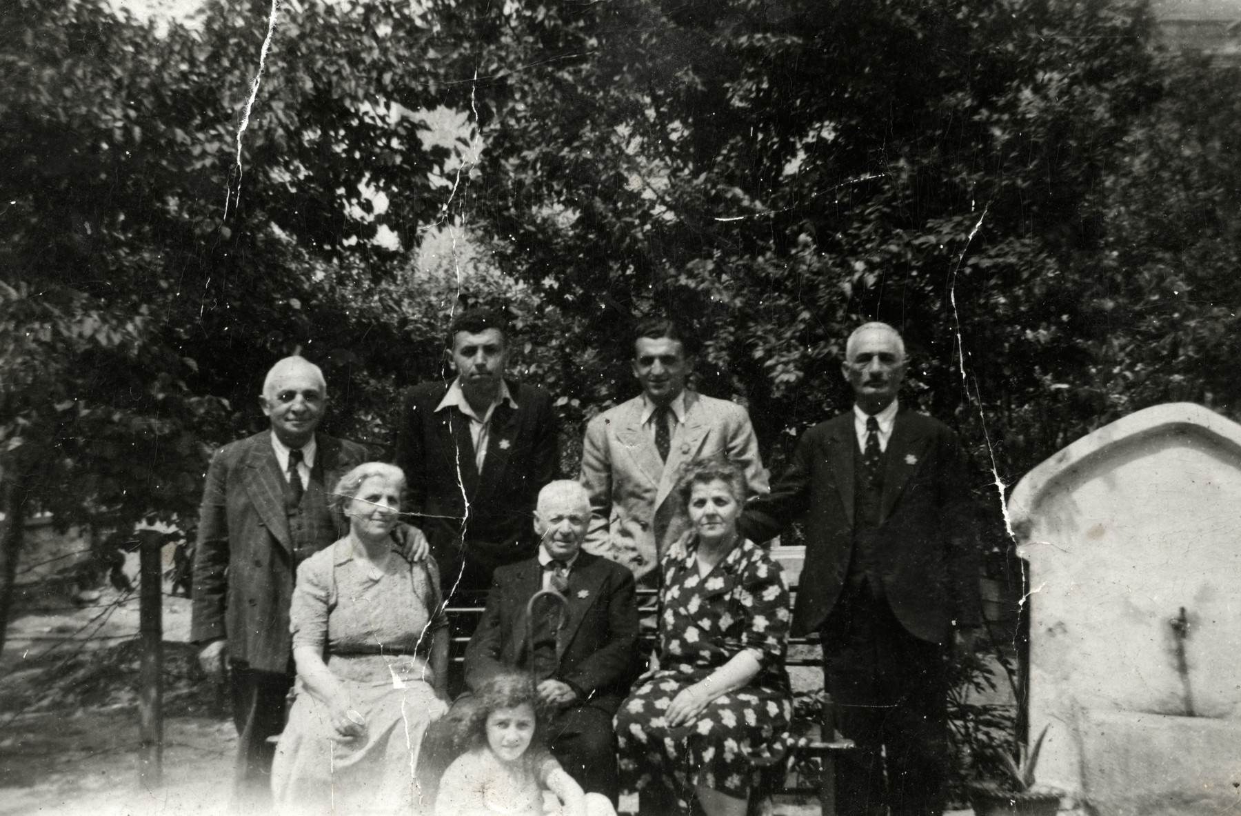 Group portrait of an extended Jewish family in Plovdiv wearing Jewish stars.  Pictured in the center is the donor's grandfather surrounded by her mother's two sisters, their husbands and other family members.