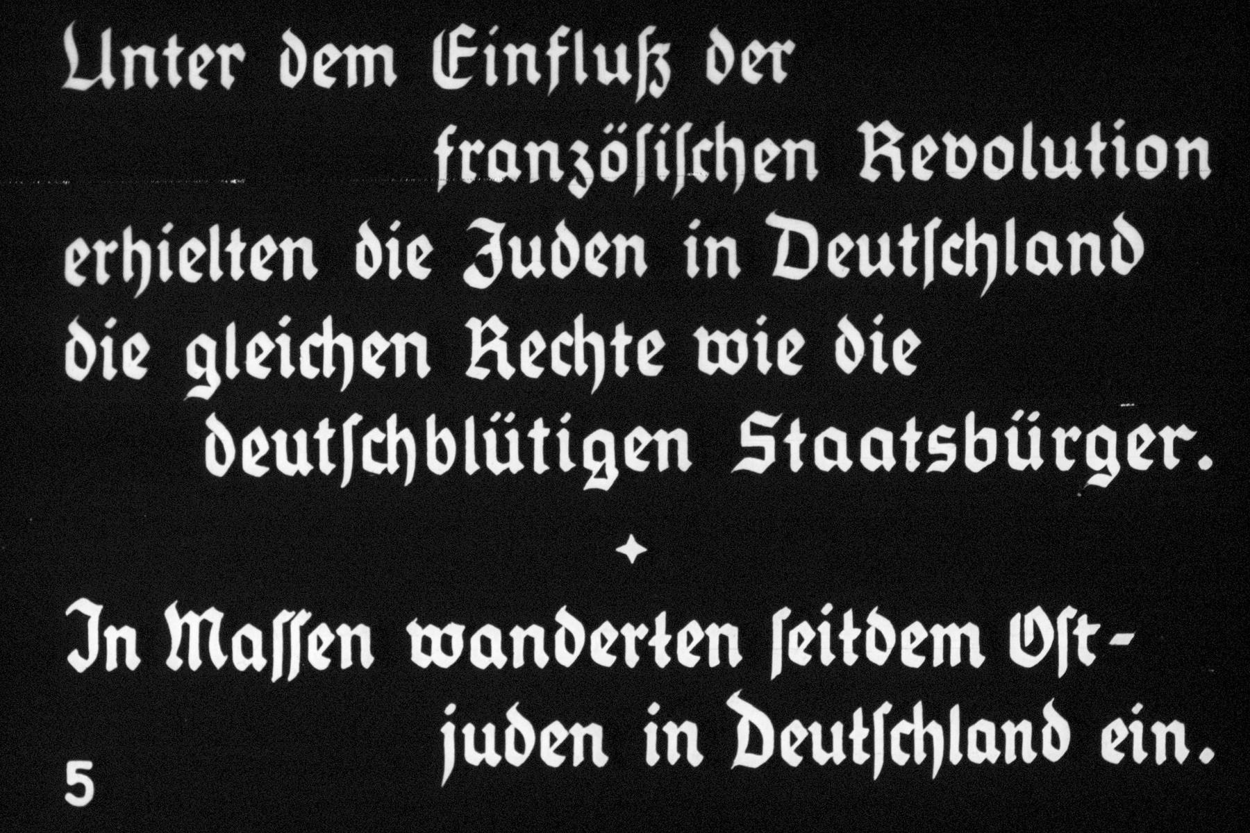 """5th Nazi propaganda slide of a Hitler Youth educational presentation entitled """"Germany Overcomes Jewry.""""  Unter dem Einfluß der französischen Revolution erhalten die Juden in Deutschland die gleichen Rechte wie die deutschblütigen Staatsbürger. In Massen wanderten seitdem Ostjude in Deutschland ein. // Under the influence of the French Revolution, the Jews in Germany recieved the same rights as the citizens of German blood. Eastern Jews then migrated to Germany in large numbers."""