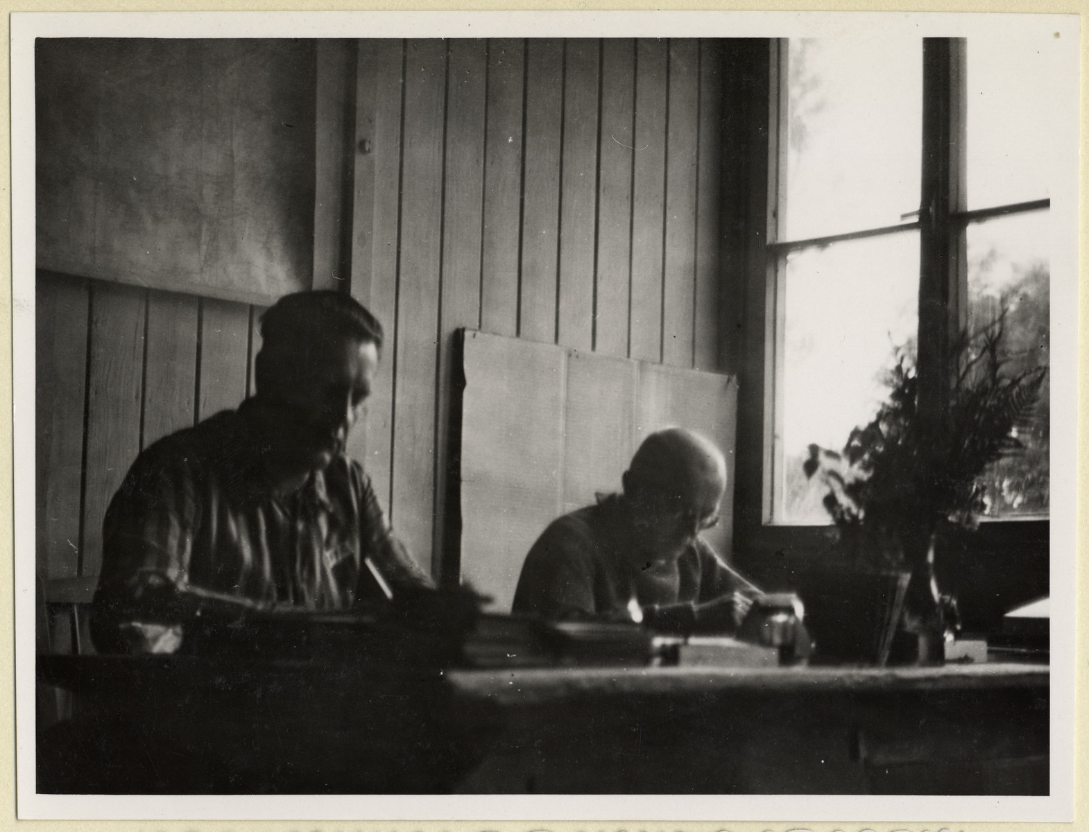 Czech political prisoners work in an office in the Dachau concentration camp.  Seated on the right is the priest, Dr. Frantisek Nemec.  The photograph was taken by Karel Kasak and developed by Maria Seidenberger.
