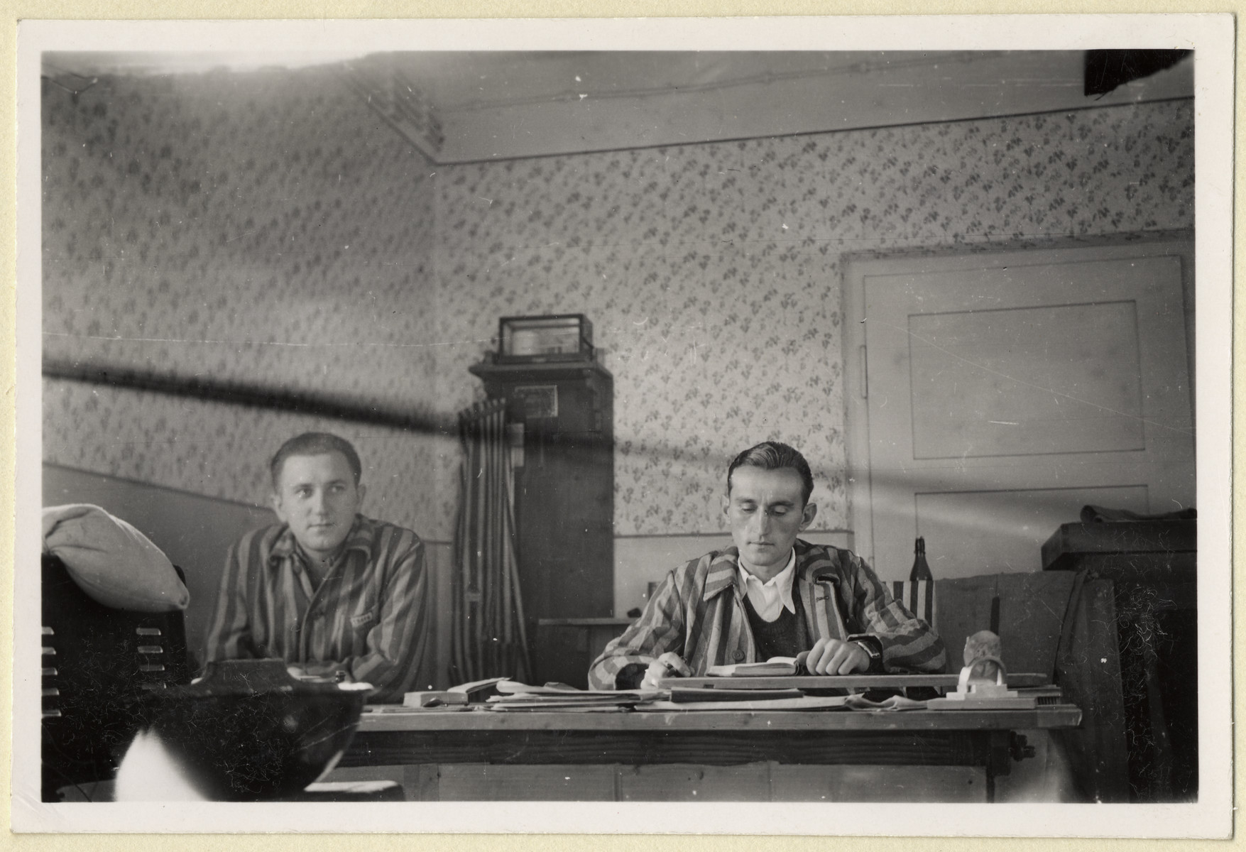 "Jiri Hell and another Czech political prisoner sit by a table in the office of the ""Plantage"" in the Dachau concentration camp.  The photograph was taken by Karel Kasak and developed by Maria Seidenberger."