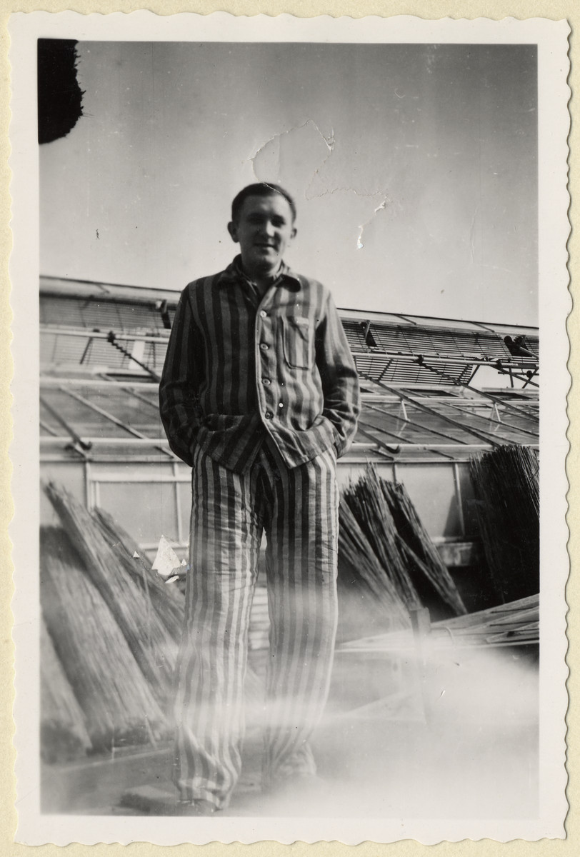 """Portrait of Jiri Hell, a Czech political prisoner standing next to the greenhouses of the """"Plantage"""" of the Dachau concentration camp.  The photograph was taken by Karel Kasak and developed by Maria Seidenberger."""