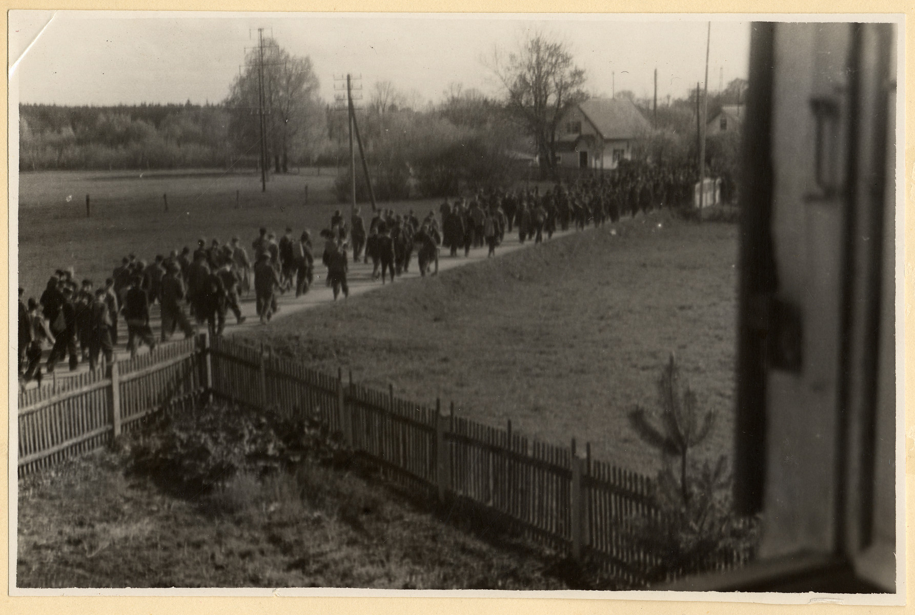 Clandestine photograph of prisoners marching to Dachau.   Maria Seidenberger took the photo from the second story window of her family's home while her mother stood outside and gave potatoes to the prisoners.