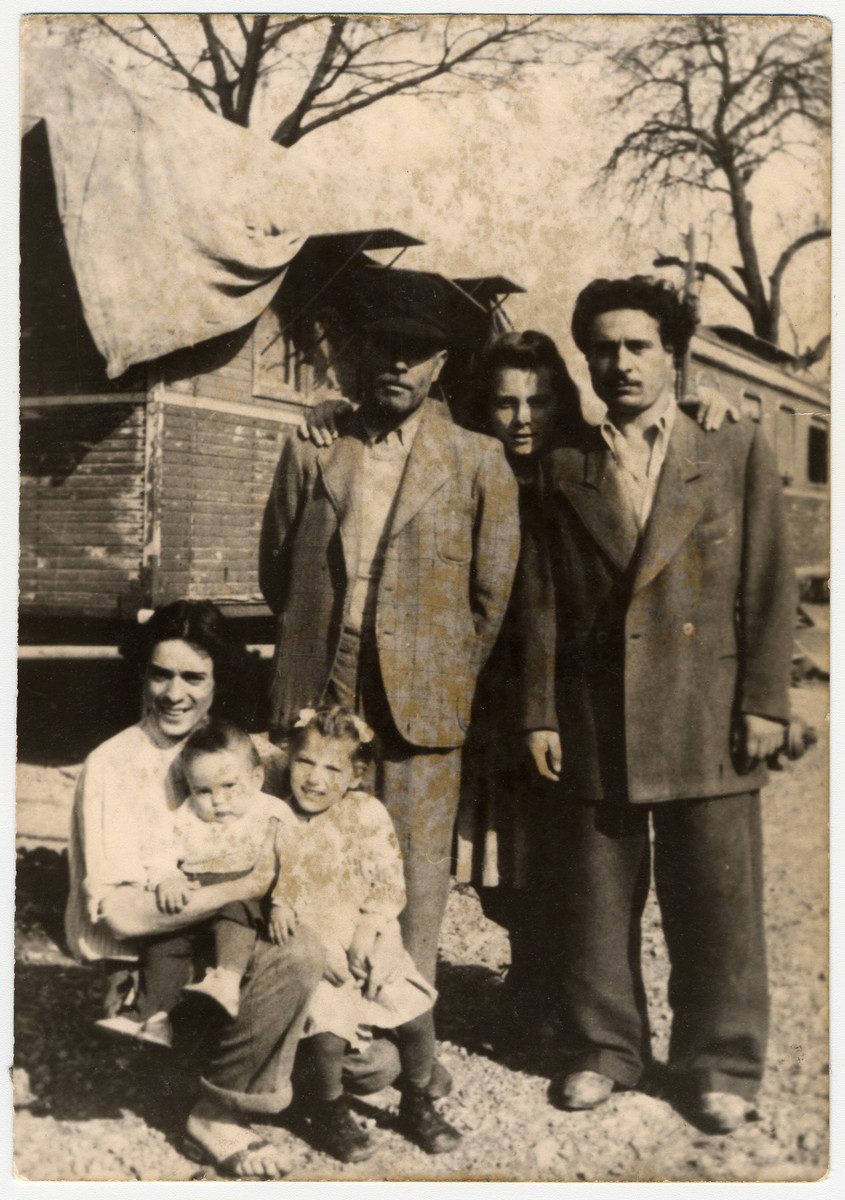 Group portrait of a Sinti (Gypsy) family in front of their caravans.   Pictured are members of the donor's family: in the middle is donor's grandfather, Johann Winterstein.  Next to him is his cousin and behind them is a German woman who was helping with the household.  Sitting is donor's uncle, Otto Winterstein, with his son Peter.  The little girl is the donor.