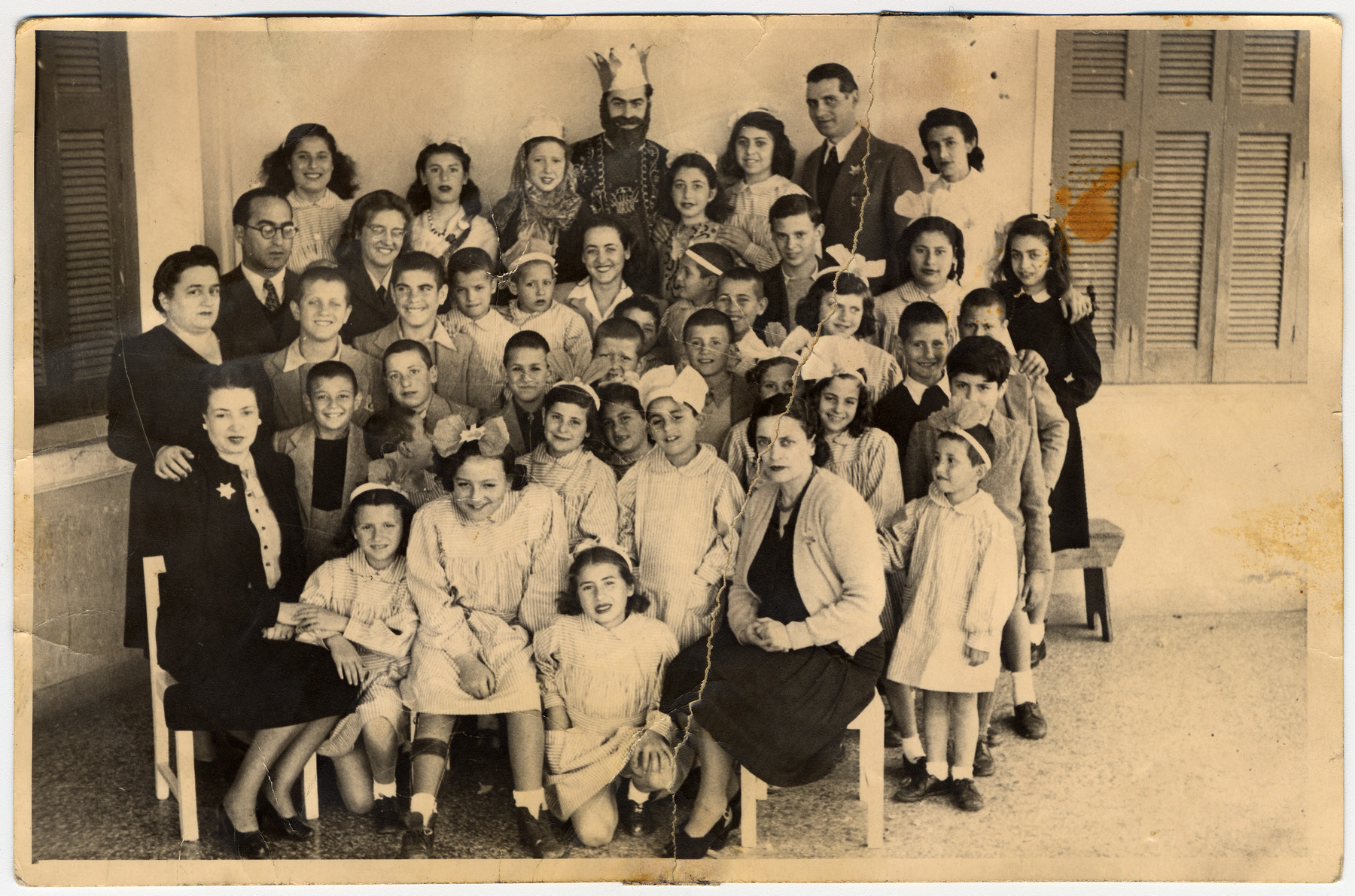 Group portrait of Jewish children and staff, some of whom are in Purim costume, in an orphanage in Athens.  Among those pictured re Evelyn and Mary Ackos.