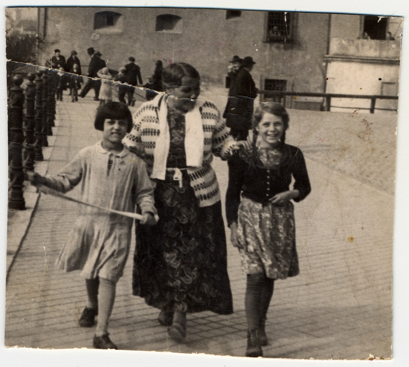An elderly Romani woman walks down a street accompanied by two girls.   Pictured is donor's mother Theresia Seible (on the right) with her grandmother and her cousin.