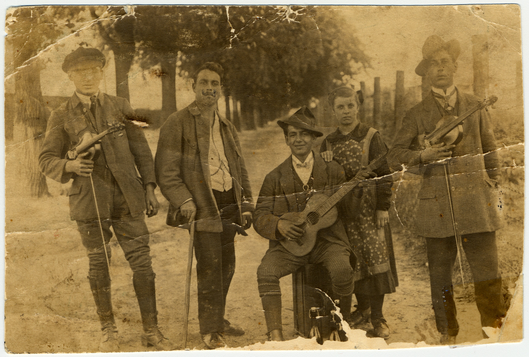 Members of a French-Hungarian Gypsy musical band pose for a photograph with their instruments.    Pictured are members of the donor's family: in the middle, with the cane, is donor's grandfather, Johann Winterstein.  Surrounding him are his cousins.  The band was mostly performing in France.