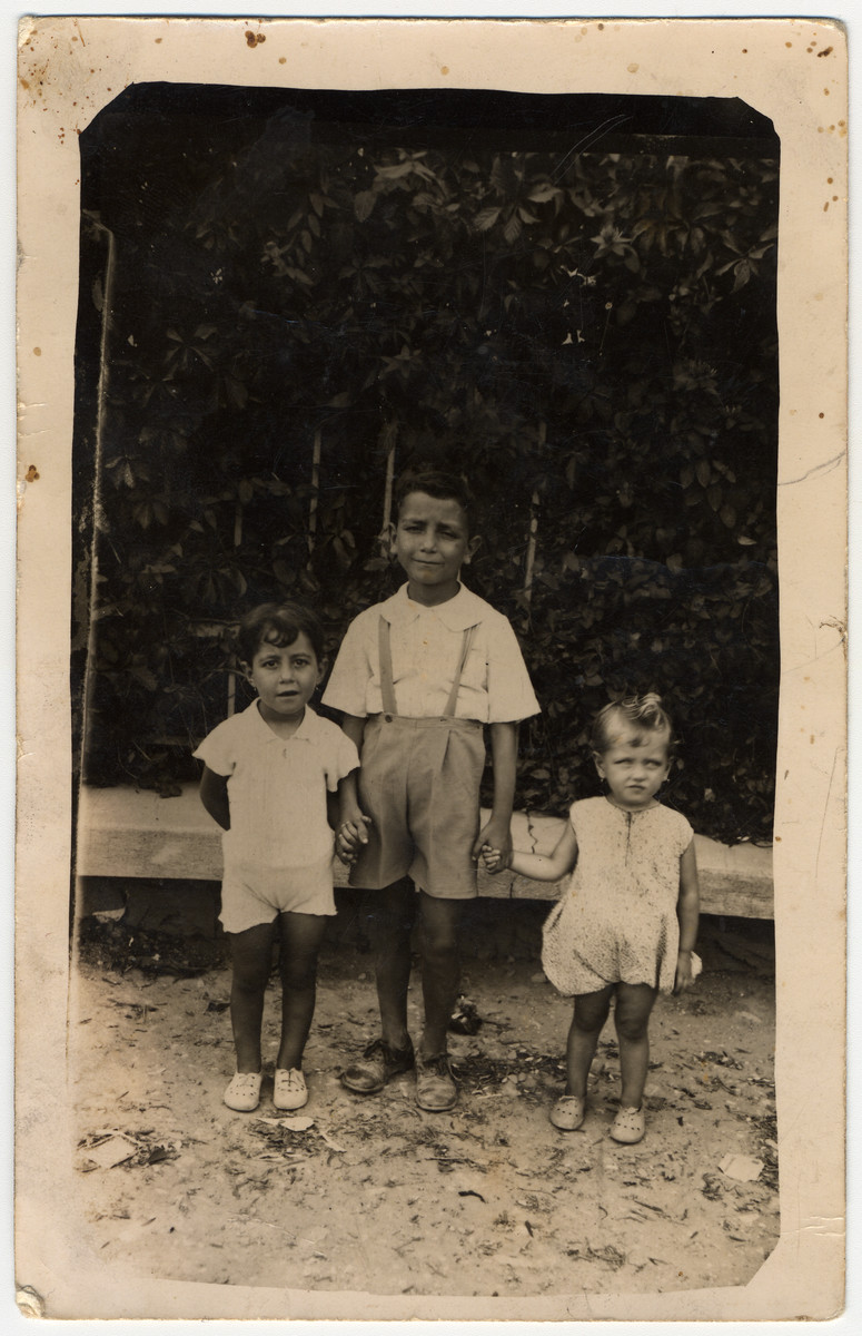 Three Greek Jewish siblings stand together outside.  Pictured are Esther, Simantov and Havoula Ackos