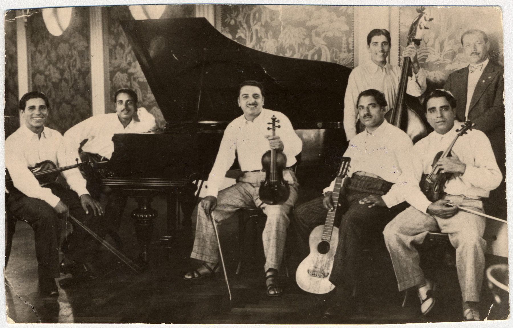 Members of a French-Hungarian Romani musical band pose for a photograph with their instruments.    Pictured from left to right are: Gabriel Reinhardt (donor's father), Benjamin (donor's uncle), Johan (donor's uncle), a cousin, Ben (donor's uncle), Josef (donor's uncle) and unknown [maybe another cousin].  The band was banned and all its members were sterelized in Wuerburg.
