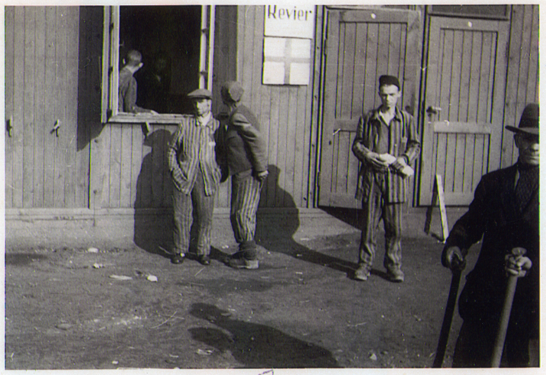 Survivors of the Hanover-Ahlem concentration camp stand outside of the infirmary.