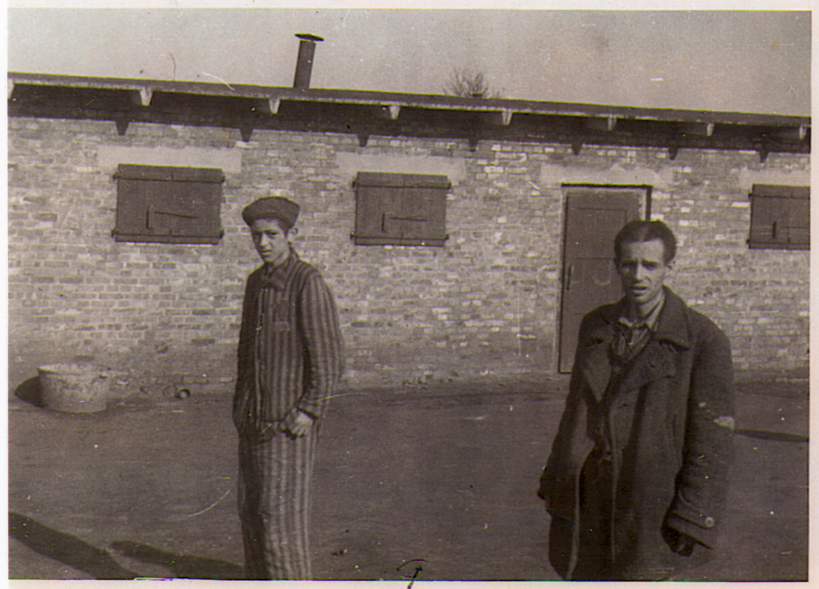Two survivors of the Hanover-Ahlem concentration camp stand in front of a barrack.