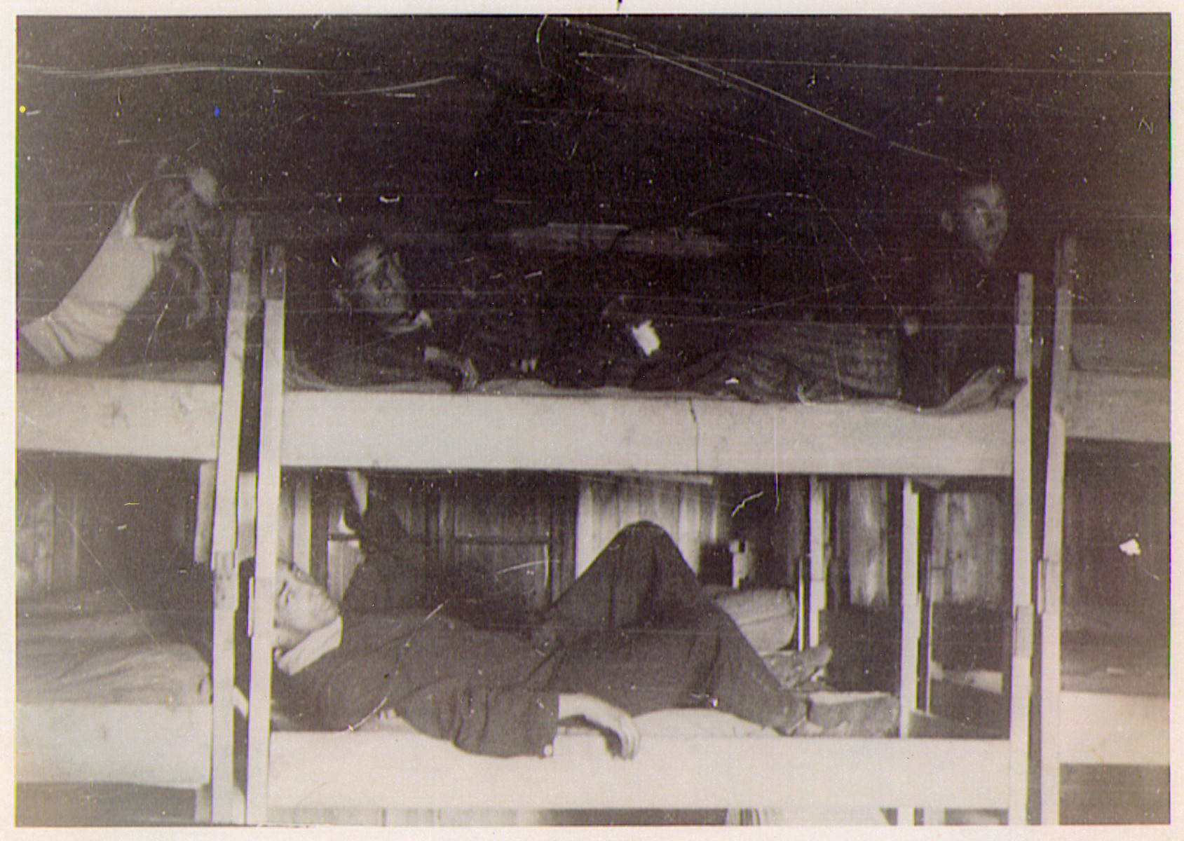 Survivors of the Hanover-Ahlem concentration camp rest in their bunks inside of a barrack.