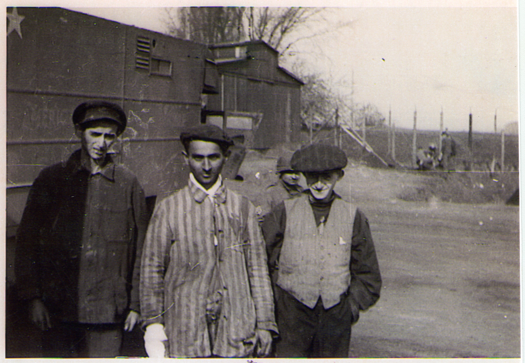 Three survivors of the Hanover-Ahlem concentration camp pose in front of a truck.  Behind them, an American soldier can be seen.