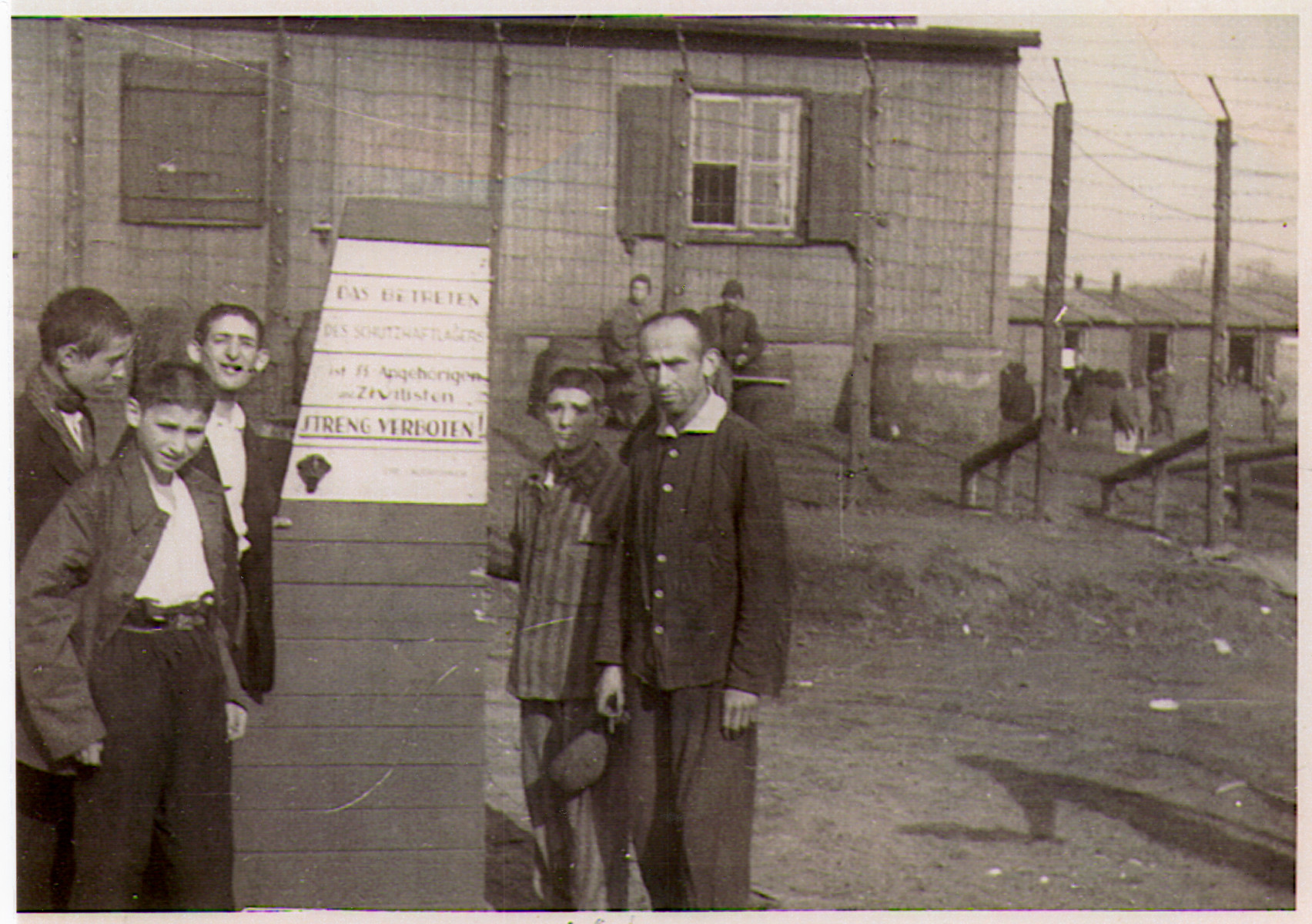 "A group of survivors, including many children, stand in front of the barbed wire fence at the entrance to the Hanover-Ahlem concentration camp.  The German sign posted in front of the fence reads ""The entrance to the prison camp by relatives of the SS and civilians is strictly forbidden."""