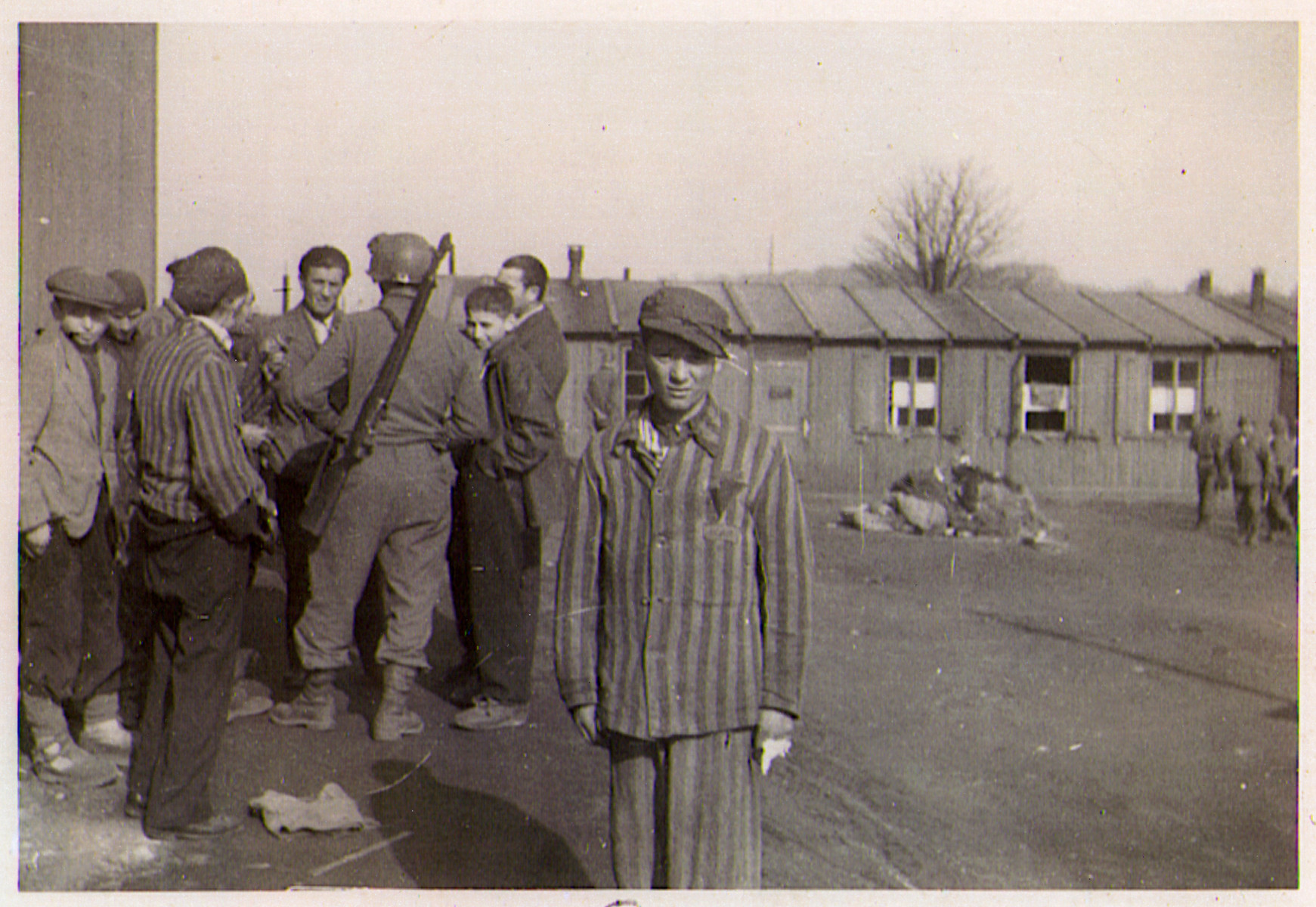A young survivor of the Hanover-Ahlem concentration camp poses in front of a group speaking to an American soldier.
