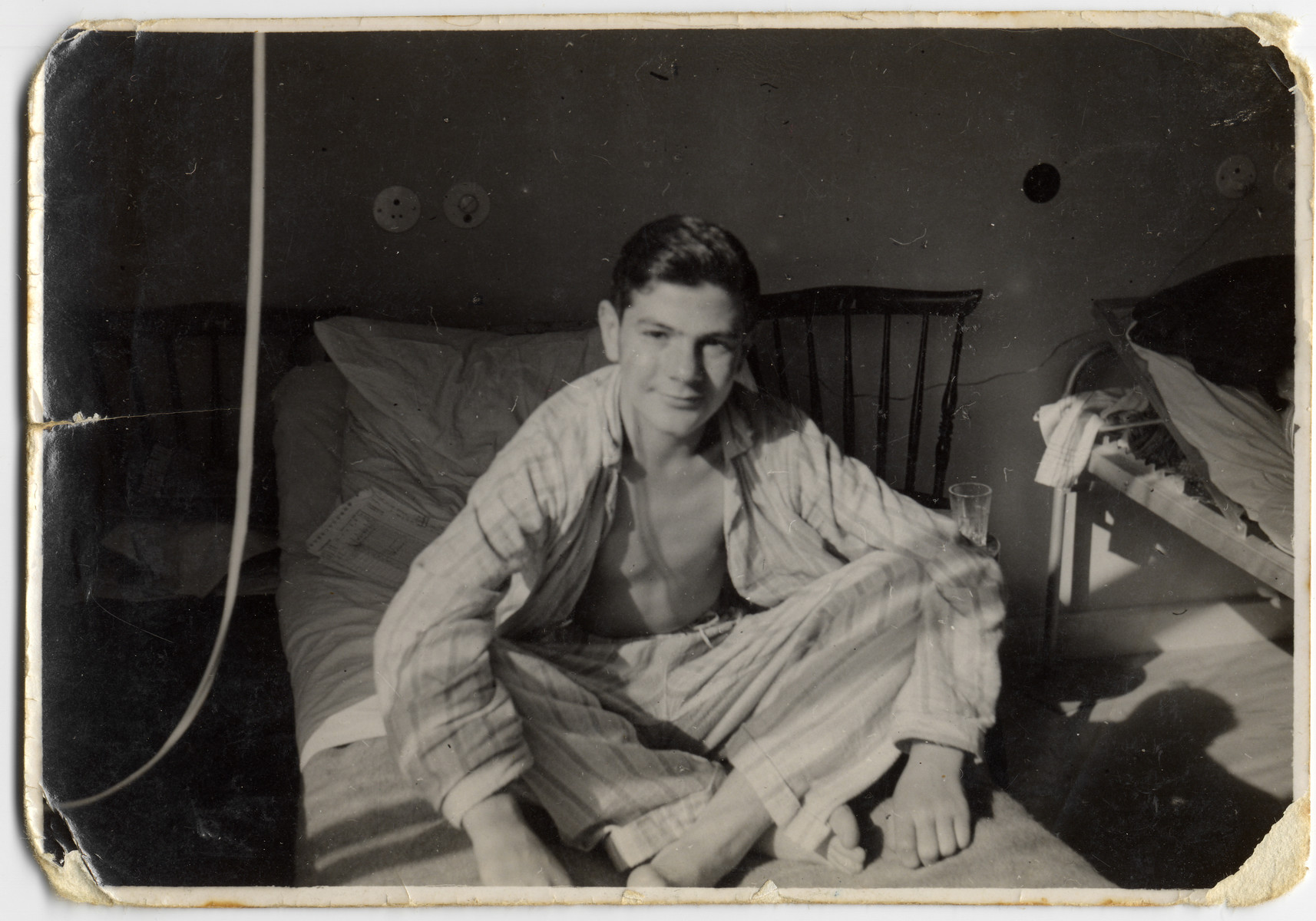 Close-up portrait of Chaim Kozienicki sitting on a hospital bed where he is recuperating in Sweden.