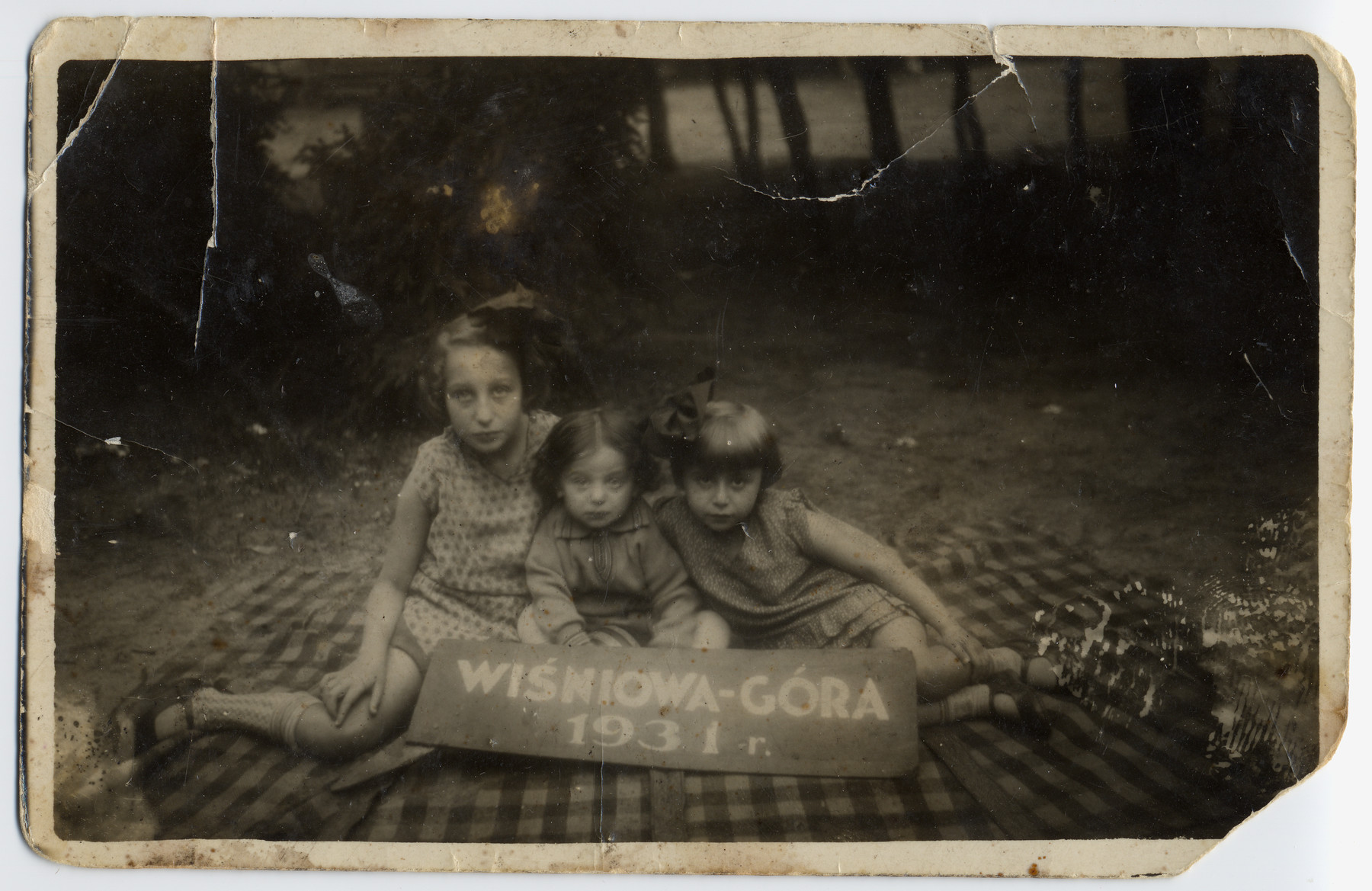 Three little girls sit on a blanket during a vacation in Wisniowa-Gora.   Pictured from the right to the left are Halina Gozdzik (later Milich), Helka Natanowicz and her sister Cela.