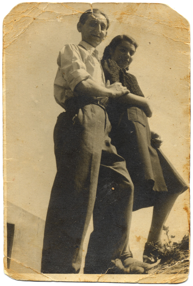 A young Jewish couple pose together in the Lodz ghetto.   Pictured is Josef Szwarc (later Schwartz) with his friend Lola Blauweis.