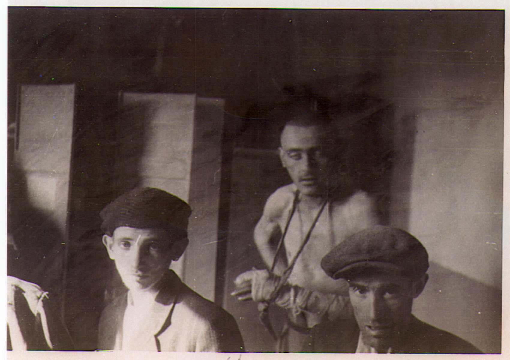 Survivors of the Hanover-Ahlem concentration camp pose inside of a barrack.