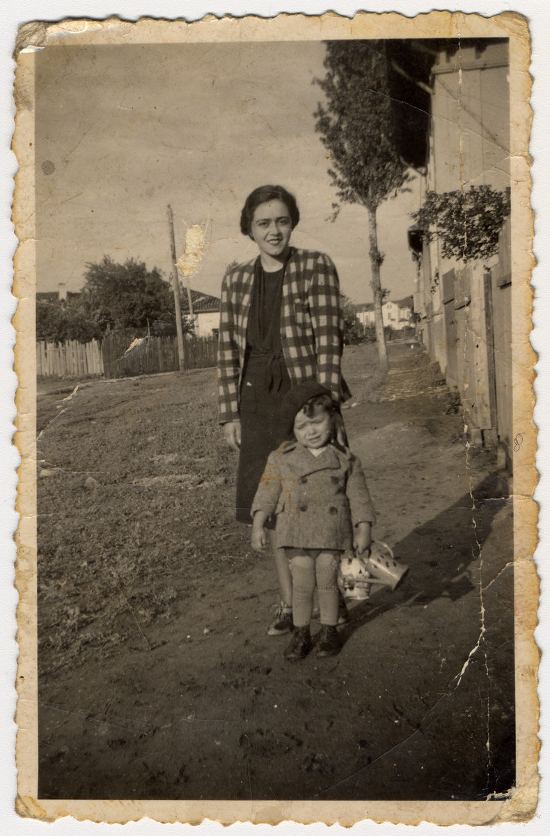 Portrait of a Jewish woman and her young son standing in front of a fence.  Pictured are Victoria and Misha Avramoff.