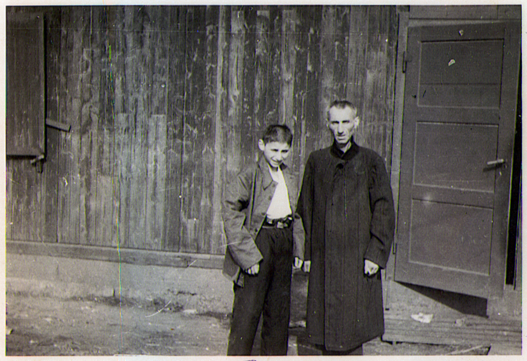 Two survivors, a man and a boy, pose outside of a barrack.of the Hanover-Ahlem concentration camp.
