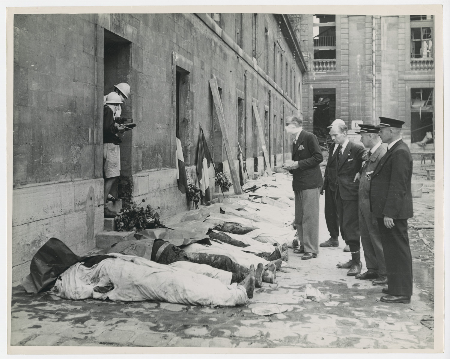 """French Red Cross workers try to identify the bodies of French forces murdered outside the Chateau St. Vincennes.    Original caption reads: """"French Red Cross workers seek identification papers on the bodies of members of the French Forces of the Interior who were murdered after being held captive in the Chateau St. Vincennes, famous old fort in Paris.  Panicked by the advance of the U.S. forces, the Germans dug pits, brought their French prisoners out in batches of 15 and machine-gunned them.  After the liberation of Paris, the bodies were disinterred for identification and respectable burial""""."""