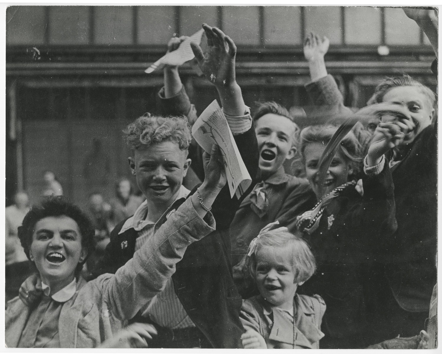 """Dutch citizens celebrate the liberation of Utrecht.  Original caption reads:  """"Crowds celebrating victory in the streets of Utrecht, Holland, are fired on by Nazi fanatics hiding in a building overlooking the parade.  After a sharp skirmish, the Germans were captured by Dutch patriots and the celebration was resumed.  Here, as the Nazis open fire on the victory crowds, Dutch patriots go into action""""."""