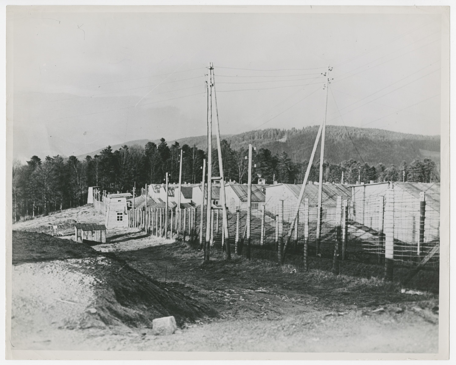 """A view of the Struthof concentration camp in Echirmeck, France.  Original caption reads:  """"This is a view of the Struthof concentration camp in the Echirmeck area of France.  Barbed wire fencing encloses the crude buildings where 8,000 French patriots are reported to have been gassed by the Germas and then cremated in huge ovens""""."""